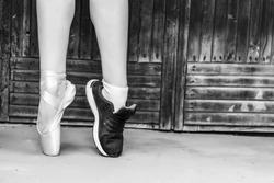 Feet dressed in dance pointe shoes and sports shoes. Black and white photo