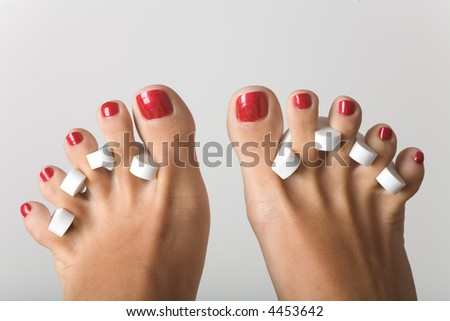 Feet during the pedicure, isolated on grey - stock photo