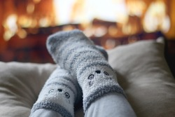 Feet in cute fuzzy socks in front of a fireplace. Selective focus.