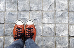 Feet in leather sneaker on pavement background, top view