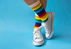 feet in rainbow socks and sneakers on a monochrome blue background