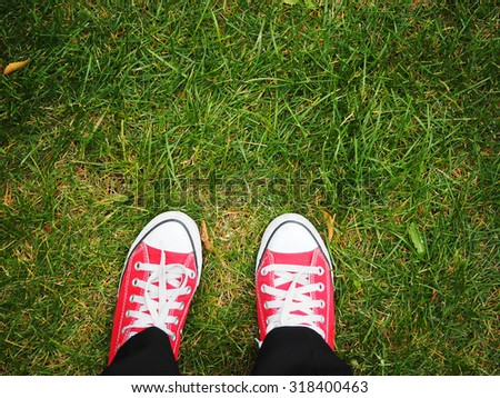 Feet in red sneakers on green grass, top view, informal style #318400463