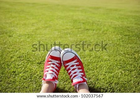 Feet in sneakers in green grass #102037567