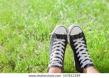 Feet in sneakers on green grass  #147812189