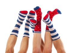 Feet in striped and dotted socks isolated over white background