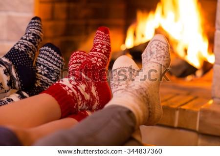Feet in wool socks near fireplace in winter time #344837360