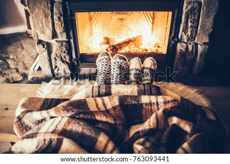 Feet in woollen socks by the Christmas fireplace. Couple sitting under the blanket, relaxes by warm fire and warming up their feet in woollen socks. Winter and Christmas holidays concept. #763093441