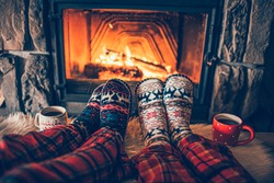 Feet in woollen socks by the Christmas fireplace. Family sitting relaxes by cozy authentic fireside with a cup of hot drink and warming up their feet. Winter and Christmas holidays concept