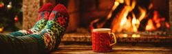 Feet in woollen socks by the Christmas fireplace. Woman relaxes by warm fire with a cup of hot drink and warming up her feet in woollen socks. Staying at home. Winter and Christmas holidays concept.