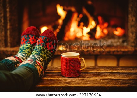 Feet in woollen socks by the Christmas fireplace. Woman relaxes by warm fire with a cup of hot drink and warming up her feet in woollen socks. Close up on feet. Winter and Christmas holidays concept. #327170654