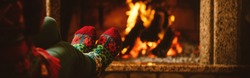 Feet in woollen socks by the fireplace. Woman relaxes by warm fire and warming up her feet in woollen socks. Staying at home during quarantine. Winter and Christmas holidays concept. Banner format.
