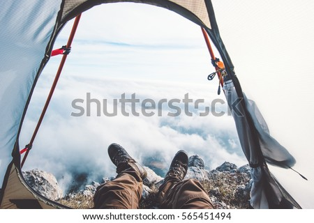 Feet Man relaxing enjoying clouds mountains aerial view from tent camping entrance outdoor Travel Lifestyle concept adventure vacations outdoor
