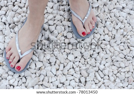 feet of a caucasian woman wearing red nail-polish and flip-flops