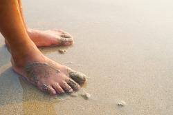 Feet of a child on the sand beach