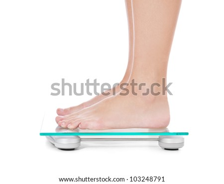 Feet of a female person standing on weight scale. All on white background.