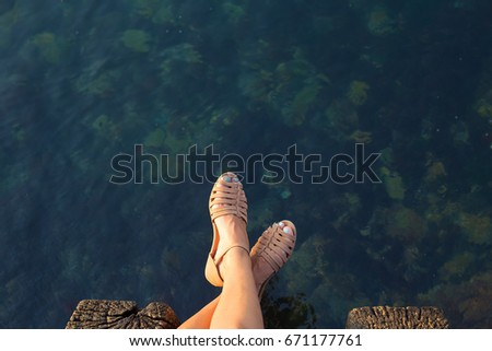 Feet of a girl who sits on a pier #671177761