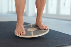 Feet of a man working out on a balance board in a gym to strengthen and tone his muscles in a low angle view