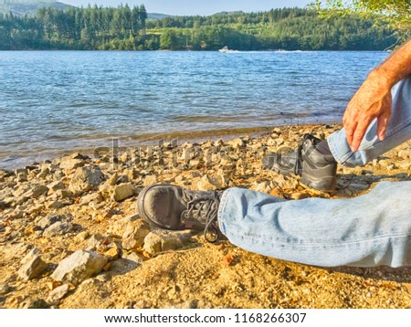 Feet of a resting man in heavy shoes against a background of blue water on the beach. #1168266307