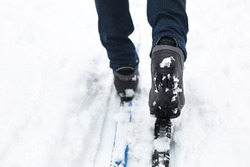 Feet of a skier in ski boots on cross-country skis. Walking in the snow, winter sports, healthy lifestyle. Close-up, copyspace