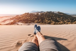 feet of a traveler in shorts and hiking shoes on the background of a paradise landscape with golden sand and blue sea in the background. Wellbeing and exploration concept