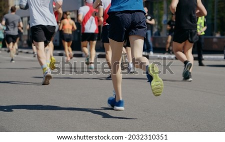 Feet of athletes running marathon in city, onlookers on roadside. Partial view from behind of contestants of sports event. Healthy lifestyle. Concept of sport Foto stock ©