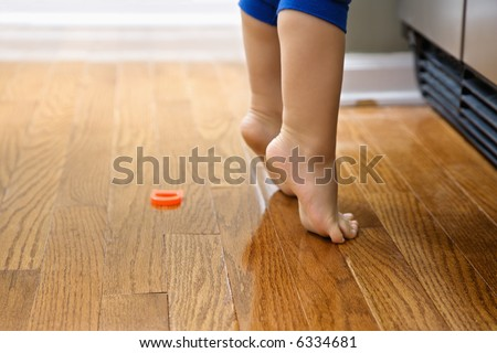 Feet of Caucasian toddler boy with magnets in front of refrigerator.