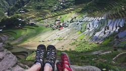 Feet of couple hikers siting and watching rice terraces from top of hill above Philippine  village  Batad