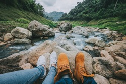 Feet of couple relaxing while sitting look at the view of mountain river and forest landscape during vacation. Travel concept