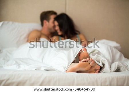 Feet of couple under blanket. Caucasian man and woman indoor. Romance and home comfort.