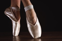 Feet of dancing ballerina on a black background in bright light