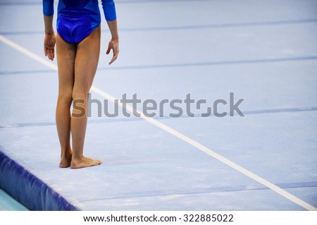 Feet of gymnast are seen on the floor exercise before gymnastics competition