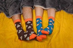 Feet of man and woman in funny socks on yellow bedsheet with grey plaid. Socks with food patterns design. Sleep, relaxation, home clothing or relashionship concept.