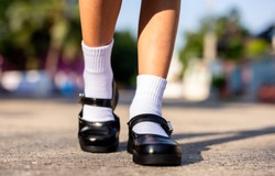 Feet of Thai girl wear a black student shoes on concrete. Concept back to school