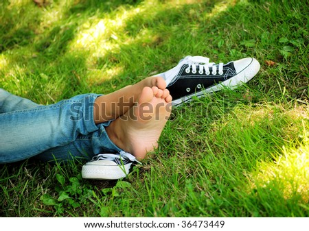 feet of the girl teenager and gym shoes on a green grass of a lawn in ...