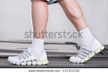 feet of the guy in sneakers on a racetrack in fitness club