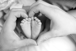 Feet of the newborn in the hands of mom close up. Heart. Mom and her child. A beautiful conceptual image of motherhood.