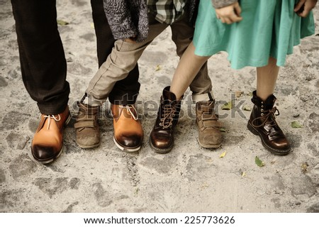 feet of three people in the autumn shoes, father, son, daughter