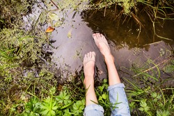 Feet of unrecognizable woman sitting at the lake.