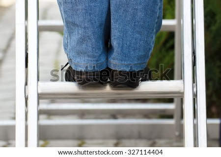 Feet of woman in black shoes on aluminum ladder in garden