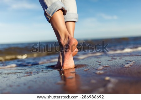 feet of woman  in the sea waves on sunset