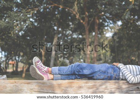 Feet of young girl sleep in the park on nature, Relax time on holiday concept travel , color of hipster tone #536419960