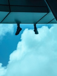 Feet of young man who sits on ledge of skyscraper, facing clouds and blue sky, for urban, travel, or psychological concepts (selective focus)