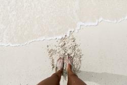 Feet on a white sand beach