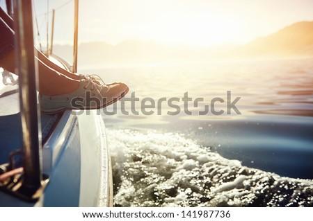 feet on boat sailing at sunrise lifestyle