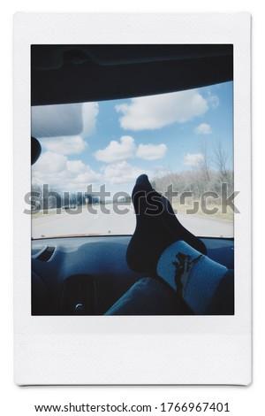 Feet on dashboard of car on highway