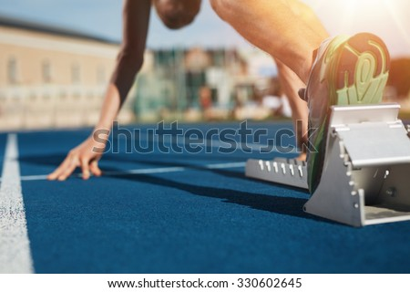Feet on starting block ready for a spring start.  Focus on leg of a athlete about to start a race in stadium with sun flare.
