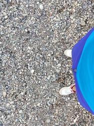 Feet on the gravel coast of a Greek beach