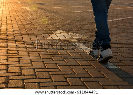 Feet on the white road arrow in the rays of the setting sun close up. Forward movement
