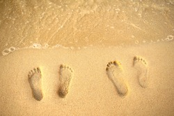 Feet prints on the sand of the beach and sea wave. Top view. Two people foot marks on sand.