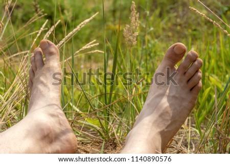 Feet resting on the beach men. #1140890576